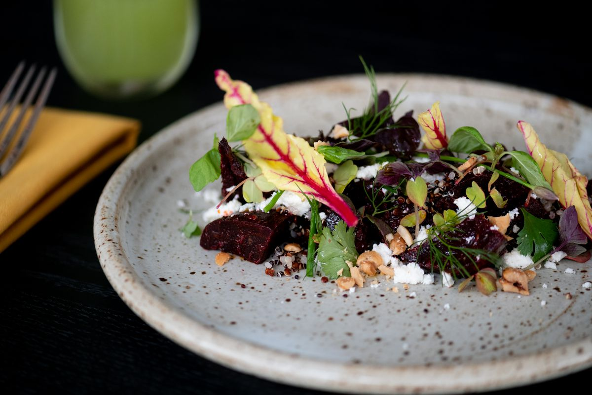 Centered in the middle of a gray, mottled stone plate are a line of dark beets tossed with crumbled white cheese, micro herbs, and nuts