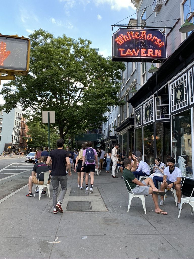 Customers sitting on white chairs on the sidewalk outside of the restaurant underneath a neon White Horse Tavern sign