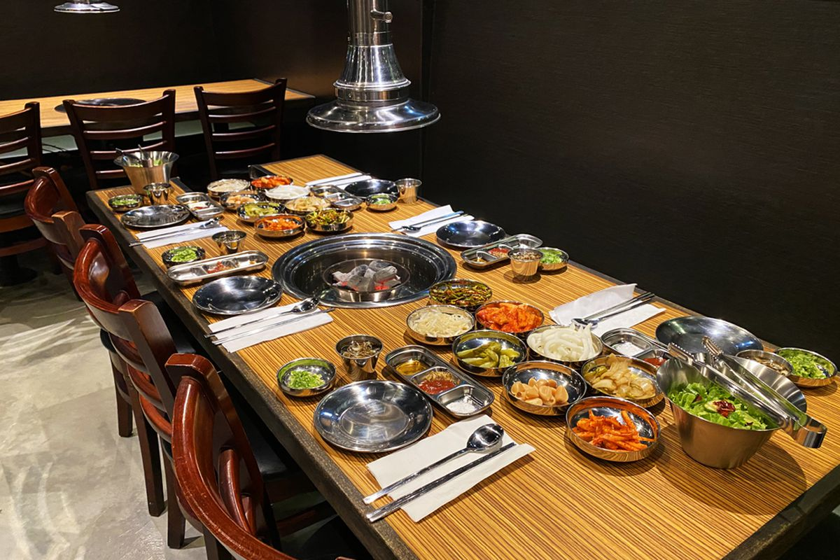 A table filled with dishes ready to be grilled a the table inside Yukga Korean BBQ.