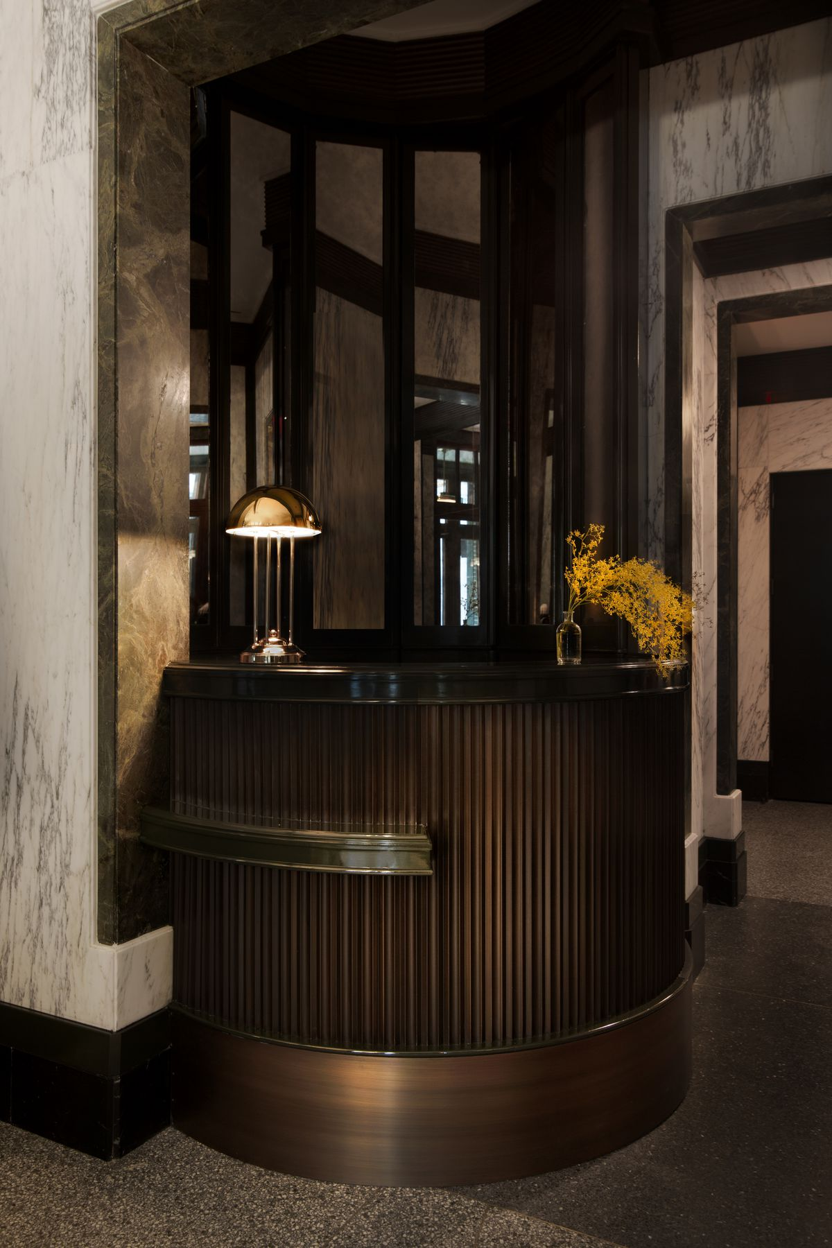 The small, rounded reception desk features a fluted carving.