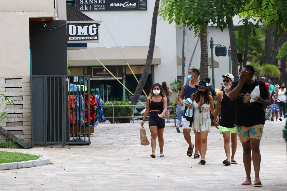 People walk past Waikiki restaurants and shops in Honolulu.