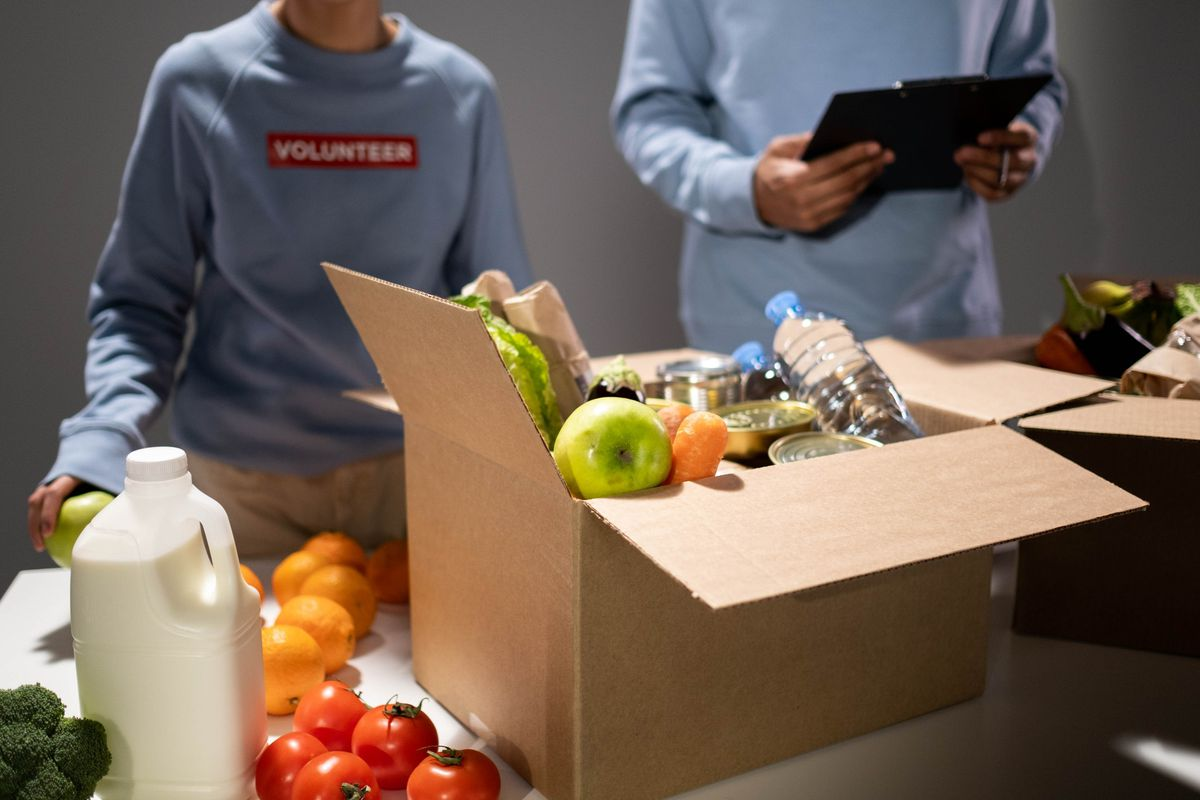 Two students are volunteering and packing boxes of food to be donated.