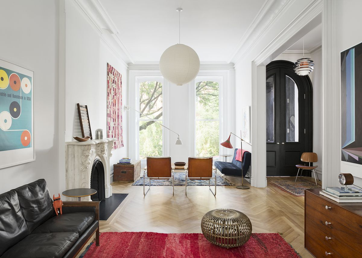 The parlor floor living room, with a vintage Hans Olsen sofa (designed in 1962) that Brent and Katie found in an antiques shop in Bed-Stuy. Vintage George Nelson-designed thin-edge cabinets for Herman Miller are paired with a bright Moroccan rug.