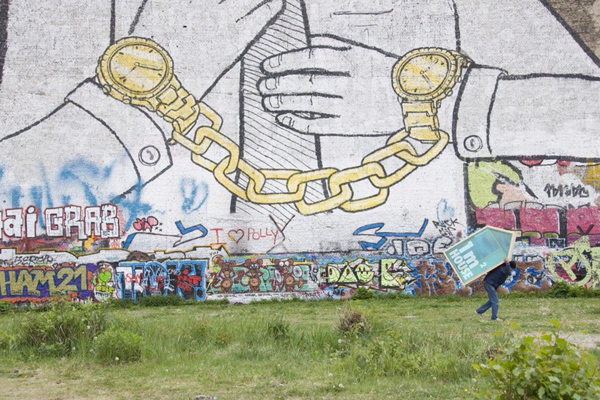 Image of a large wall with graffiti in a overgrown lot and a tiny house being carried on the back of a man.