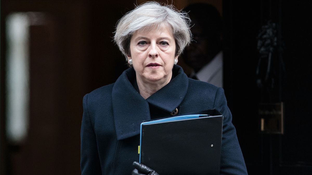 Theresa May exits a building carrying a file.