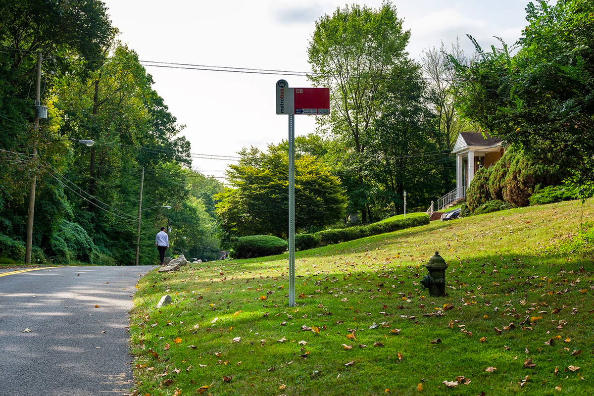 A long street with a bus stop planted in the grass. There is also a fire hydrant in the grass. In the background, a man walks in the opposite direction of the camera.