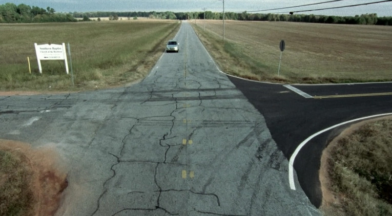 A road with one car on it. On both sides of the road are large expanses of grass.