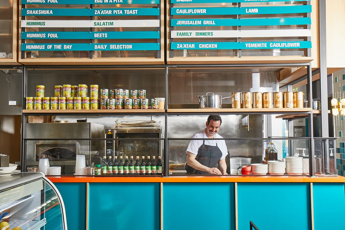 a chef behind a counter at a fast casual restaurant