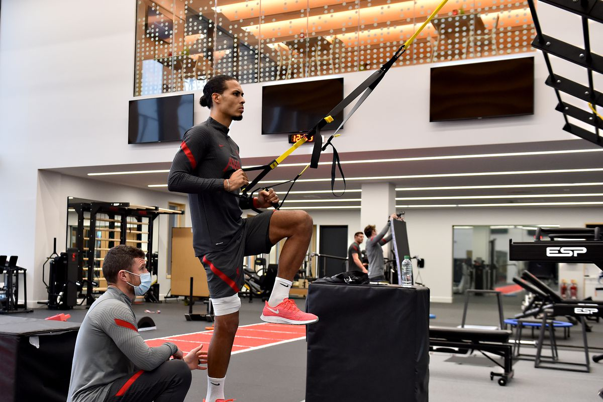 Virgil van Dijk of Liverpool during a training session at AXA Training Centre on December 04, 2020 in Kirkby, England. He lifts his knee and pulls wall-mounted bands with his arms. A masked physio staff member sits beside him to direct his movement.