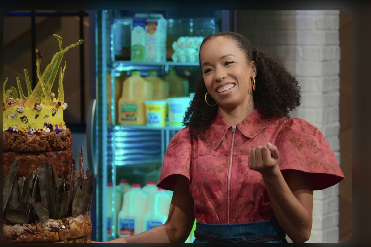 A smiling person with curly hair and a pink blouse next to a stacked chocolate cake.