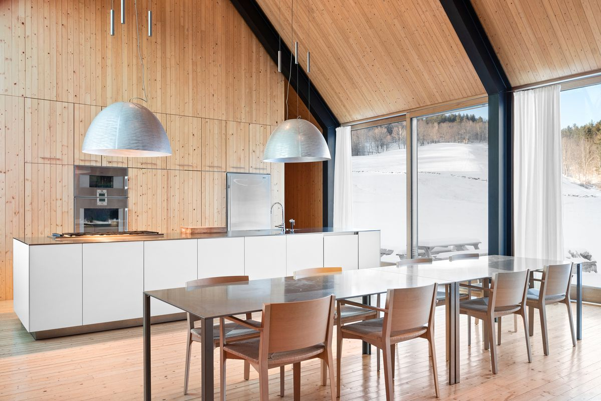 Kitchen has white counters and wood walls with a dining room table in front.
