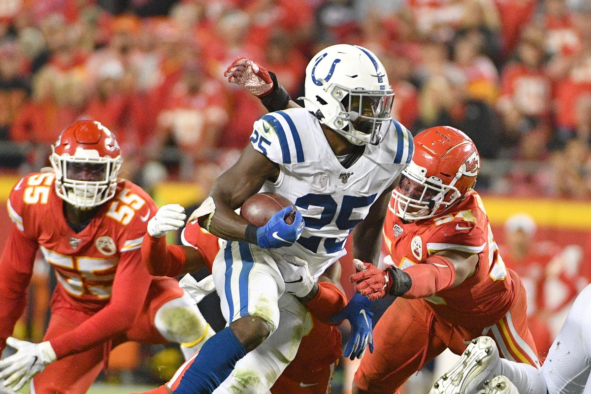Indianapolis Colts running back Marlon Mack runs the ball as Kansas City Chiefs outside linebacker Damien Wilson attempts the tackle during the second half at Arrowhead Stadium.