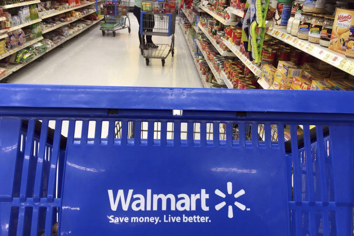 FILE- In this June 5, 2017, file photo, customers shop for food at Walmart in Salem, N.H.(AP Photo/Elise Amendola, File)
