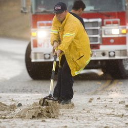 A San Bernardino County firefighter clears rocks from National Trails Highway in Oro Grande, Calif., after another thunderstorm dumped rain on the small town Monday, Sept. 10, 2012. The Highway was closed for two hours to allow the flooding to subside. The same town suffered flooding last week as well.