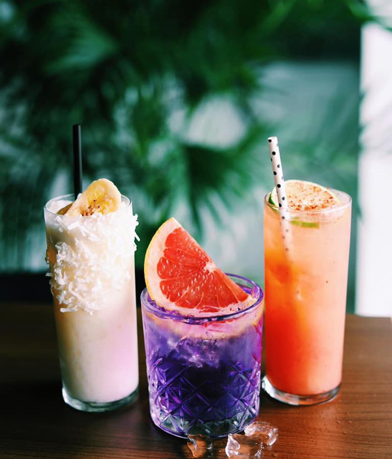 Three cocktails in creamy white, garnished with coconut, purple garnished with a grapefruit slice, and creamy orange with a paper polka dot straw