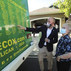 Lt. Gov. Spencer Cox shows Lue Hoffman a list of Utah cities that he has visited while running for governor during a campaign a stop in Midvale on Thursday June 11, 2020.