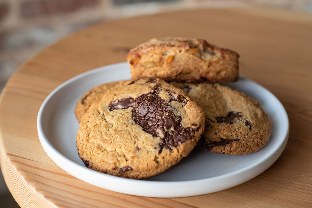 Fresh chocolate chip cookies on a plate with a scone.
