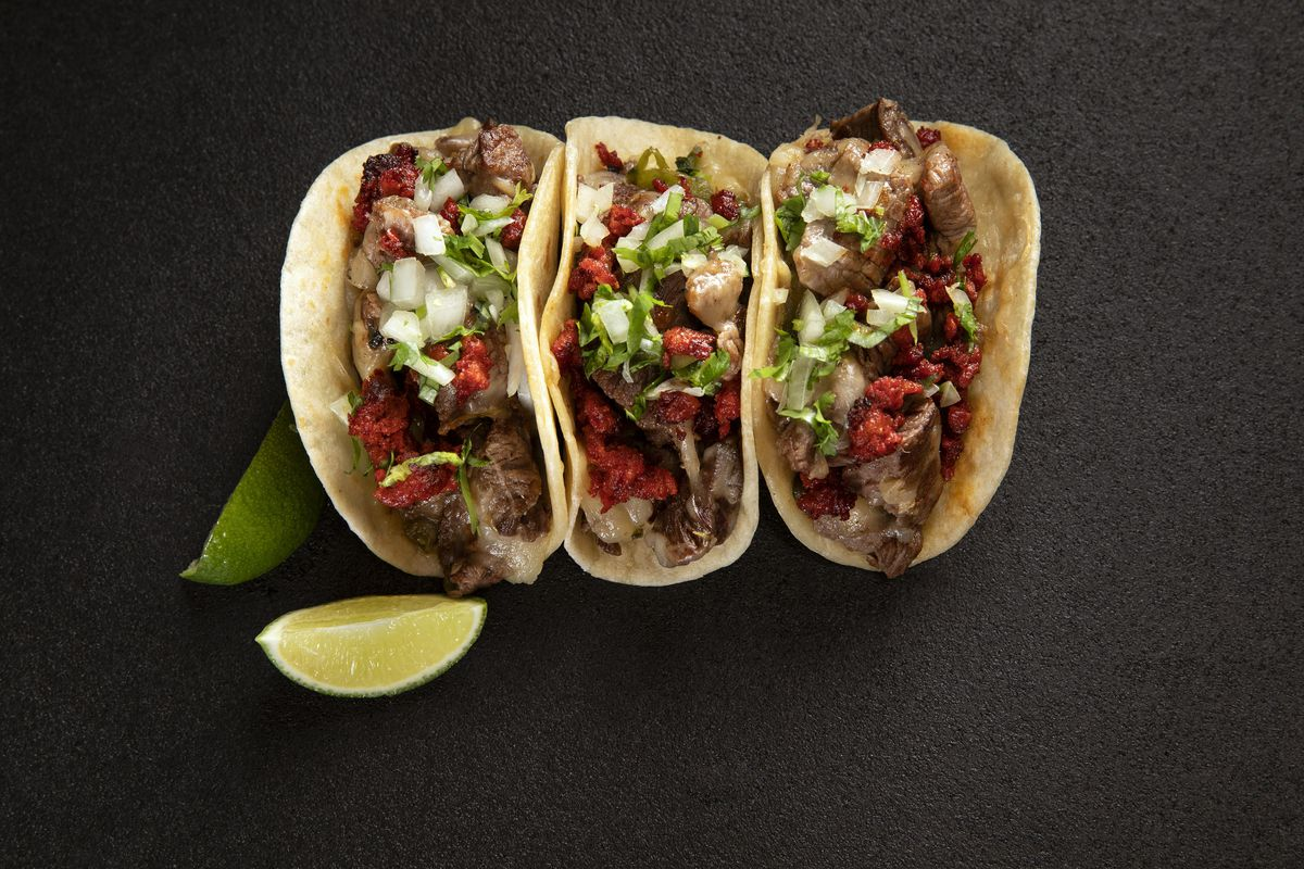 Three tacos on a black background