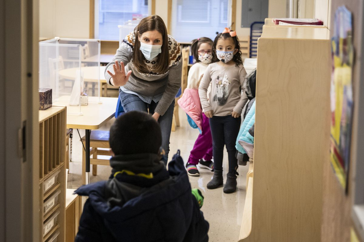 Preschool teacher Erin Berry greets students as they walk into Dawes Elementary School in Chicago, Monday, Jan. 11, 2021.