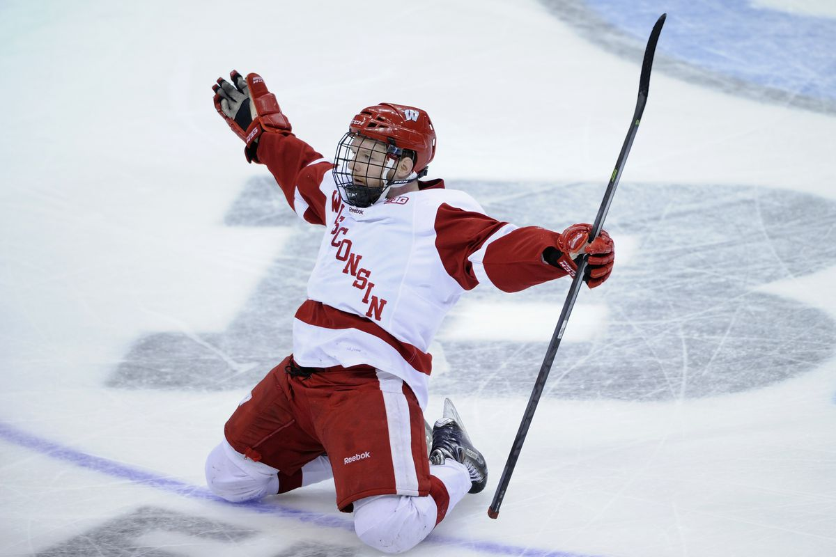"""Mark Zengerle posing in front of the """"B"""" (as in """"B1G OT goal) after winning the 2014 Big Ten Conference Hockey Tournament"""