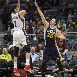 Milwaukee Bucks' Ersan Ilyasova, left, shoots a three pointer over Utah Jazz Gordon Hayward during the second half of an NBA basketball game Monday, March 3, 2014, in Milwaukee. (AP Photo/Tom Lynn)