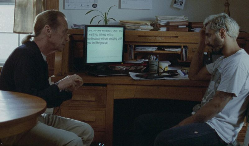 Two men sit facing one another, with a computer and equipment behind them.