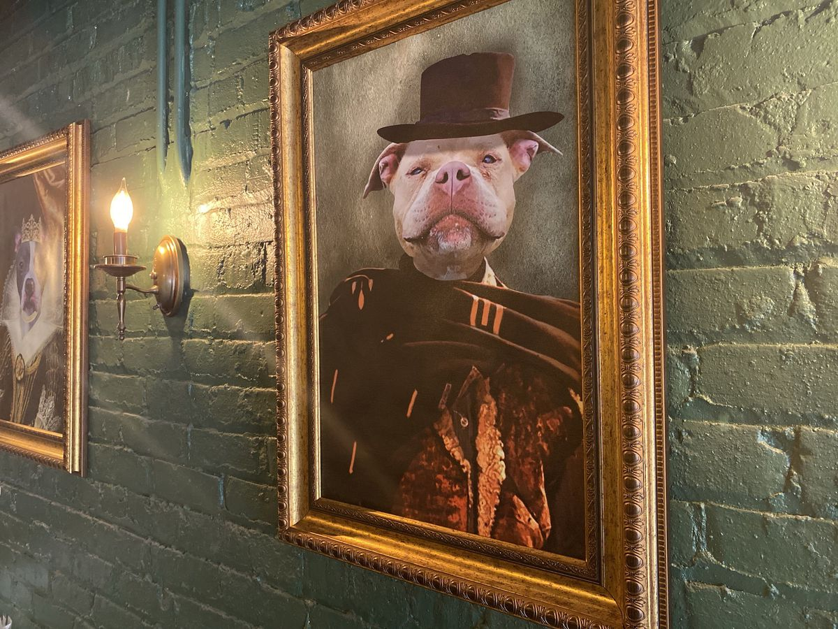 A framed photo of a dog painting.
