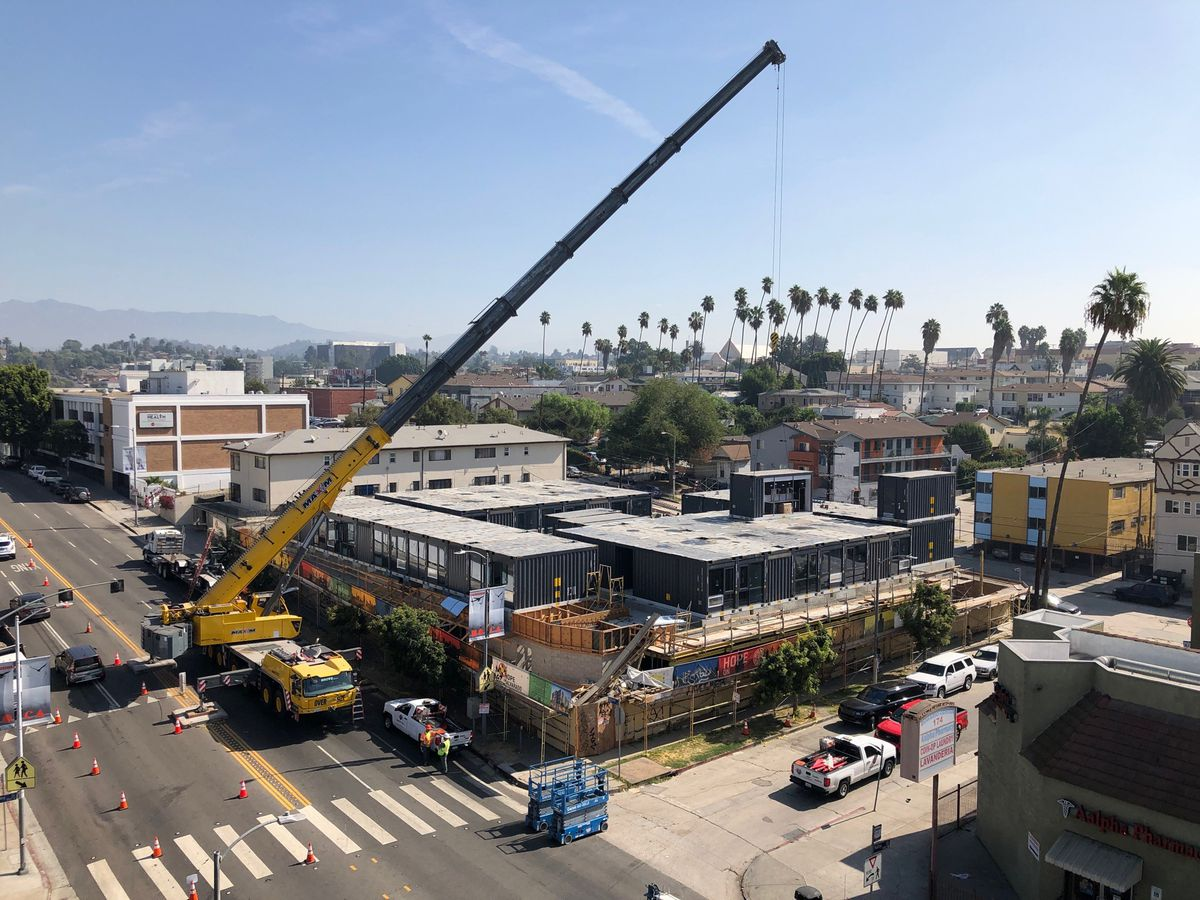 A huge crane hovers over a construction site, where gray containers are starting to form a building.