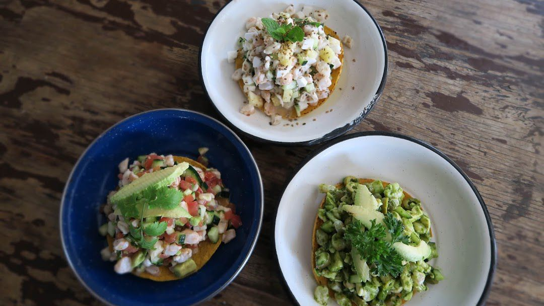 Three tostadas topped with various types of seafood arranged on on a wooden table