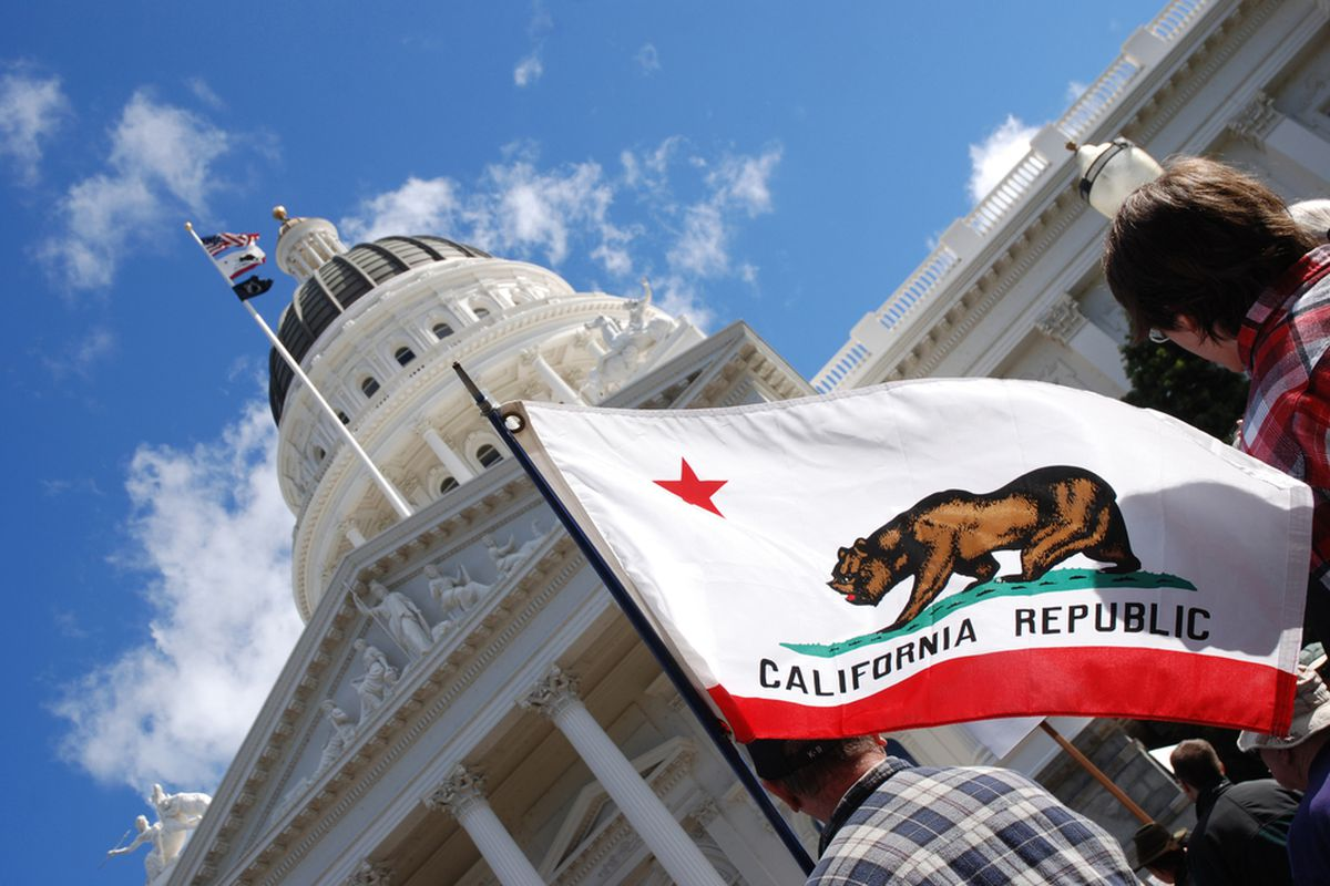 """A flag with an illustration of a bear and the words """"California Republic"""" flying in front of a building with a prominent white dome."""
