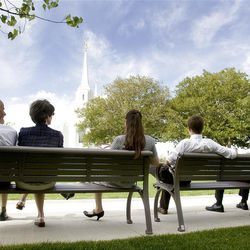 The Graff family from Layton Utah sit on benches across the street from the Brigham City Temple after the cornerstone ceremony and during the first dedicatory session Sunday, Sept. 23, 2012.