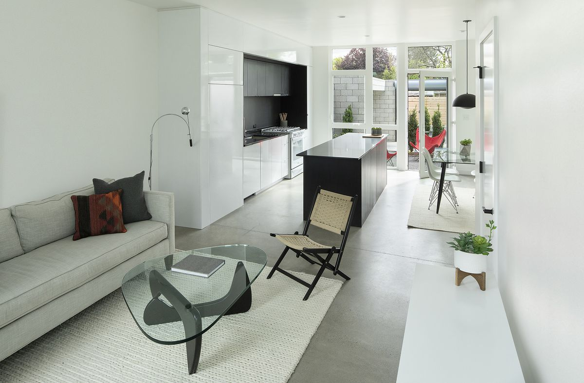 An open living room/kitchen/dining room with concrete floors, gray couch, and black kitchen island.