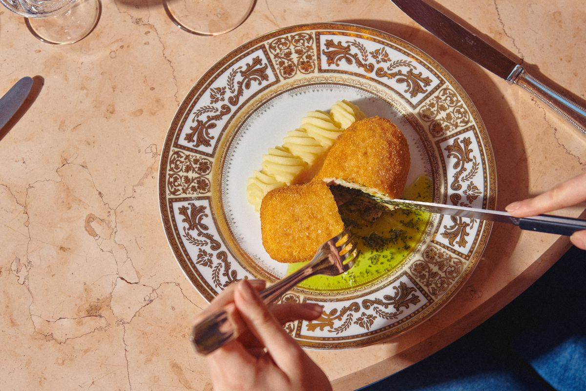 Hands holding a fork and knife cut open a beige-colored kiev with a green sauce, on an ornate plate.