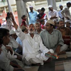 A Muslim devotee joins a group of religious singers during a qawwali performance session at Nizamuddin Dargah, a complex of tombs, mosques and stalls centered on the burial site of revered Sufi saint Nizamuddin Auliya, in New Delhi, India, Thursday, Sept. 27, 2012. On Thursday evenings, Nizamuddin's tomb transforms into a venue for a concert of devotional qawwali music. The audience sits on a wide marble courtyard in front of the tomb while singers perform hauntingly beautiful songs backed by musicians playing the accordionlike harmonium and the tabla drums.