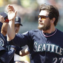 Seattle Mariners' John Jaso, right, is congratulated after scoring against the Oakland Athletics in the second inning of a baseball game Saturday, Sept. 29, 2012, in Oakland, Calif. Jaso scored on a double throwing error by the Athletics.