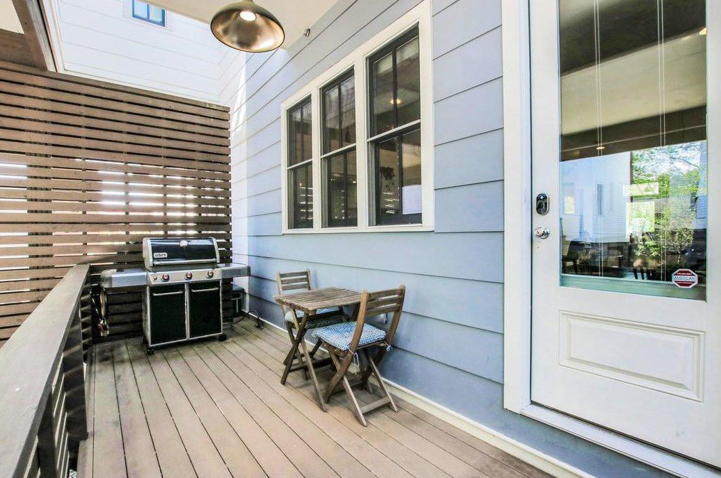 Blue siding and a light and a grilling deck.