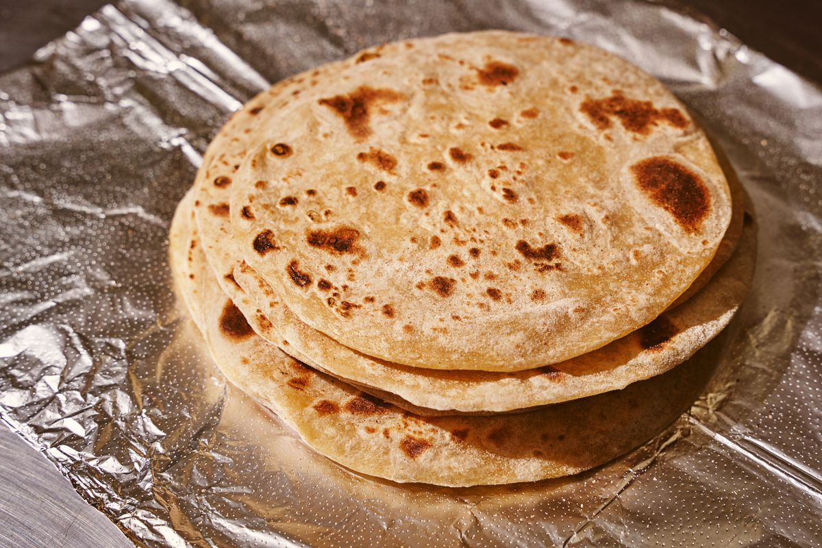 A stack of charred flour tortillas sits on aluminum foil