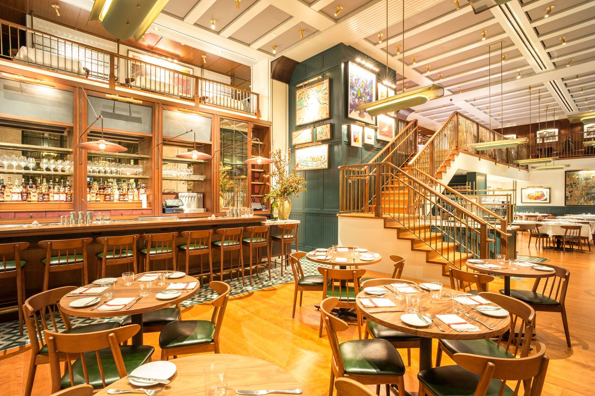 Union Square Cafe's dining room has a wooden bar, wooden chairs with dark leather seats, and stairs that go up toward another level