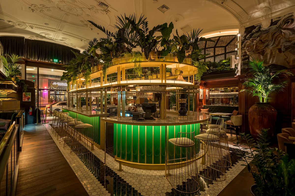 A bright green wraparound bar layered with greenery on top and gold touches.