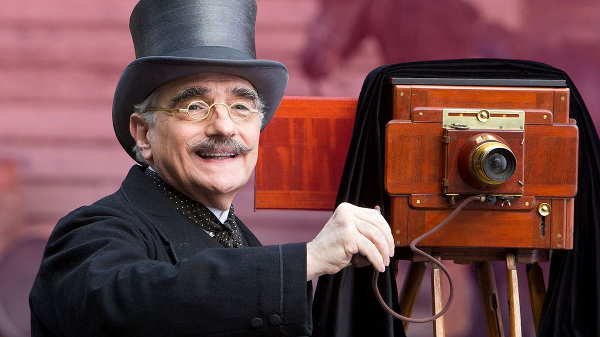 Martin Scorsese is top hat and coat with vintage camera