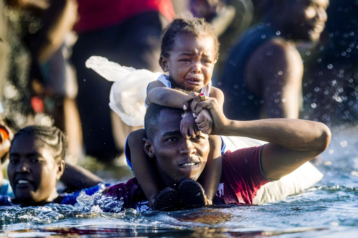 A man in water up to his armpits carries a small child on his shoulders.