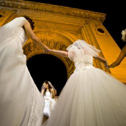 In this Sunday, Aug. 26, 2012 picture, Romanian brides dance next to the Triumph Arch in Bucharest, Romania. The arch, a replica of the Arc de Triomphe in Paris, the French capital, is a rendezvous place for brides on the wedding night for the bride stealing ritual. The ancient Romanian tradition of bride stealing is getting bigger, brasher and an increasingly common sight in the Romanian capital, the region's undisputed party town.