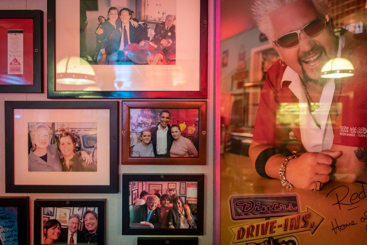 Picture frames containing photographs of Clinton, Gore, Obama, Trump, and Fieri posing for photographs with other people.