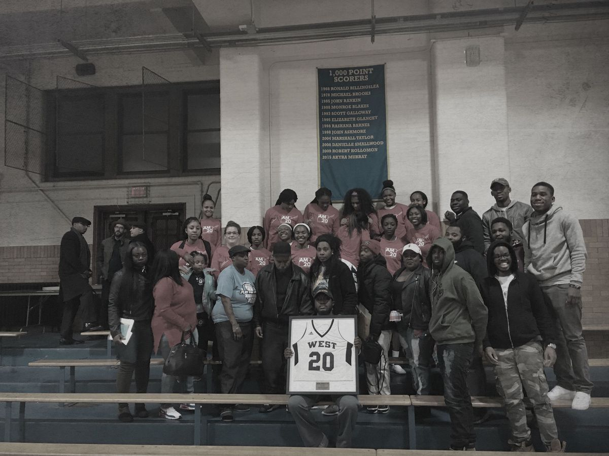 Alex, surrounded by family and friends, holds the jersey presented to his family on the night West Catholic Prep retires Akyra's number in December (Jordan RitterConn)