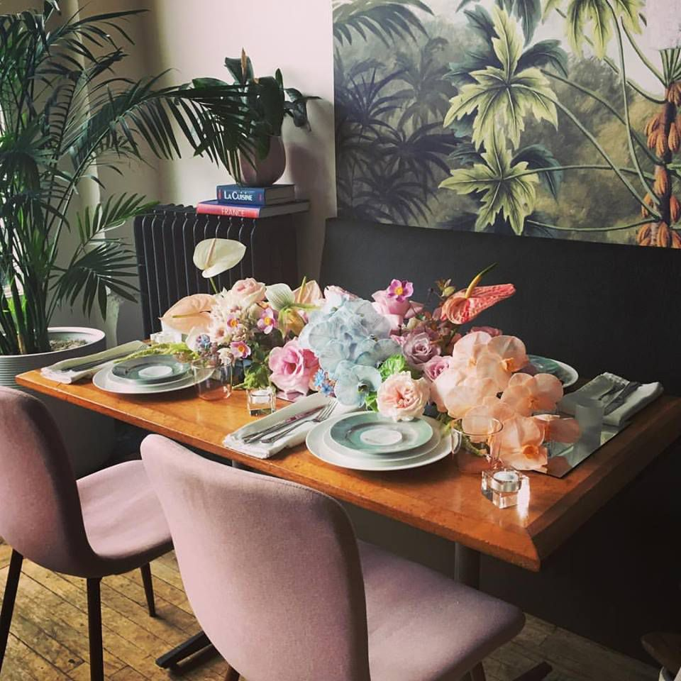 A table set with flowers in front of a green wallpapered wall