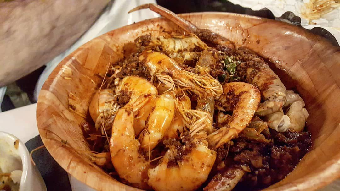 A wooden bowl filled with Cajun-seasoned seafood