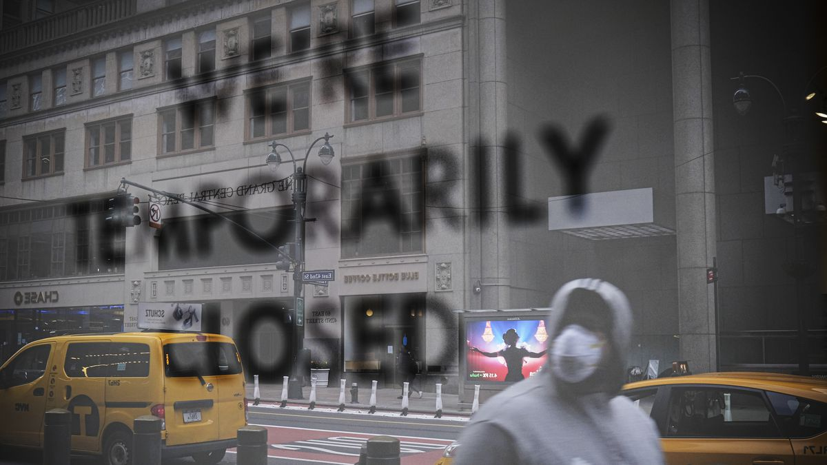 """A sign in a city window reads, """"We're temporarily closed."""" A pedestrian in a mask, two taxis, and the building across the street are reflected in the glass."""