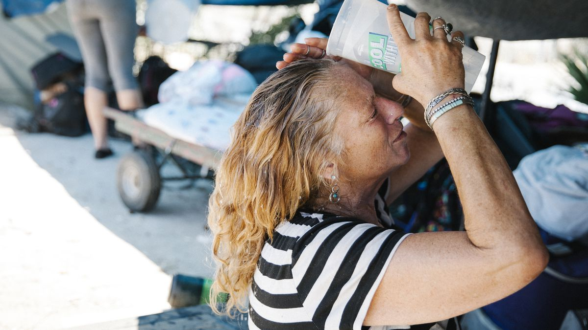 A woman with tan skin and wavy strawberry blond hair pours water from a big plastic cup over the back of her head.