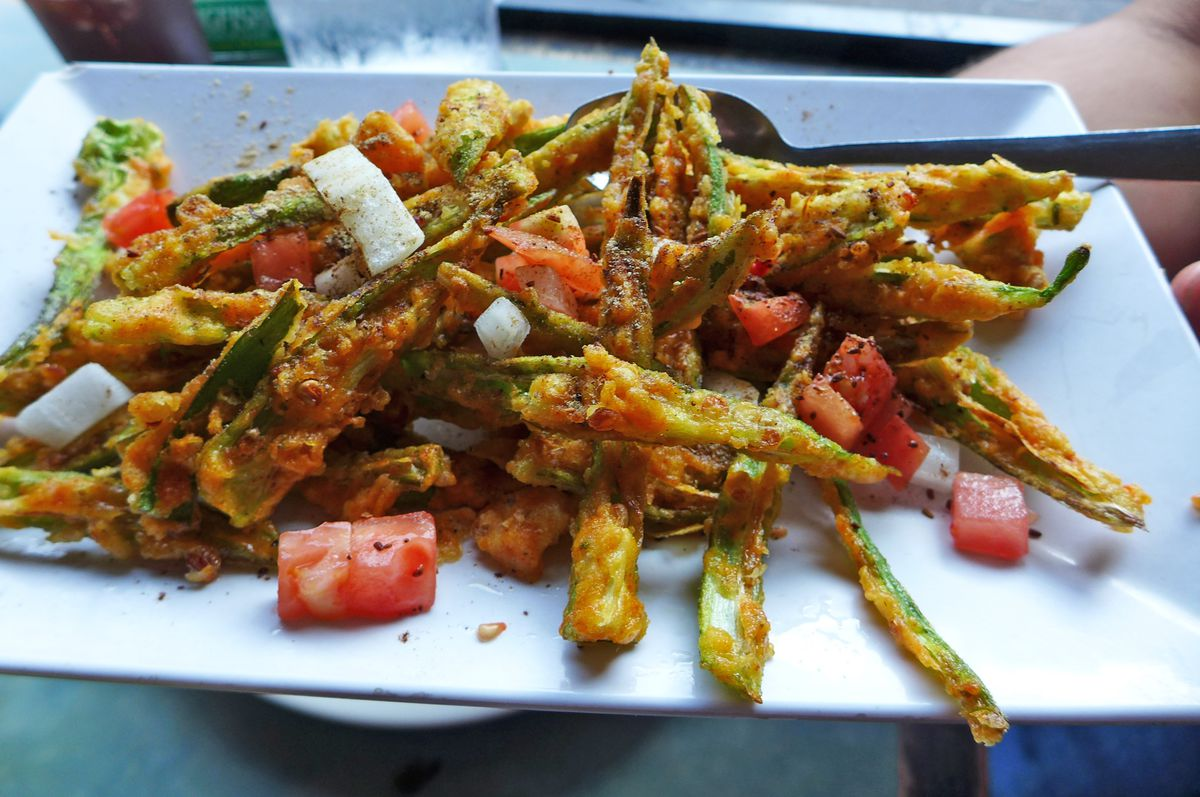A pile of shredded and fried okra tossed with cubes of tomato