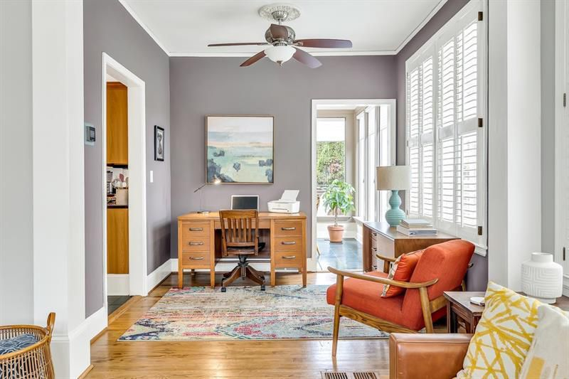 A mauve painted room with a ceiling fan and large desk.